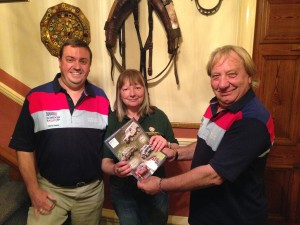 Prize-winner Cathy Hughes, holding the lucky number programme, flanked by partner Steve Castle (left) and event director Rick Smith. (Picture by Anthony Concannon)