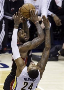Miami Heat's LeBron James (with ball) clears the Pacers' Paul George as he takes a jump shot last night.