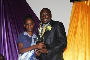Minister of Parliament Dwight Sutherland presenting a trophy of academic excellence to valedictorian Kiara Yarde.