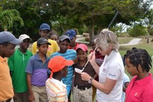 Sarah Claridge (second right) explaining the features of a golf club and the importance of correct contact to the juniors.