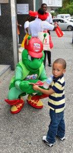 Scotiabank Kiddy Cricket mascot presenting LCPL tickets to a young fan.