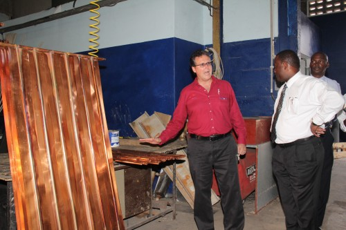 Sunpower sales director Henry Jordan (left) tells Minister of Commerce Donville Inniss about how things are done at Sunpower during a tour.