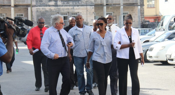 """Publisher of the Nation newspaper, Vivian-Anne Gittens (in white jacket), senior journalist Sanka Price (walking behind her) and Editor-in-Chief Roy Morris (in back, wearing black) being led to the District """"A"""" Court to answer the charges. At left is Queen's Counsel Alair Shepherd who is leading the Nation's defence team."""