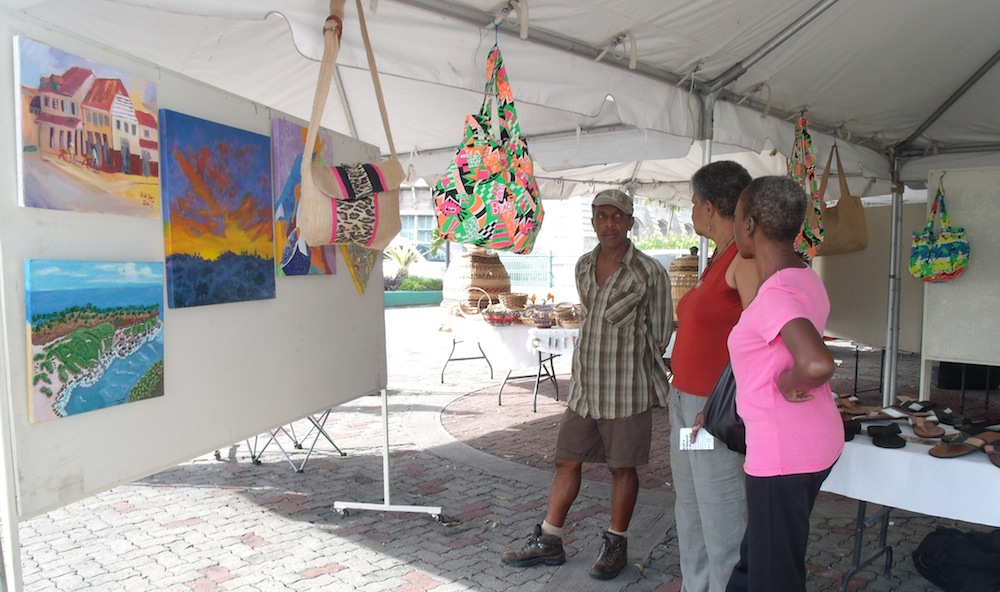 Artist Omawale in conversation about his paintings with two viewers.