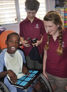 This Challenor student (left) demonstrating to his English visitors how to use his talking machine.