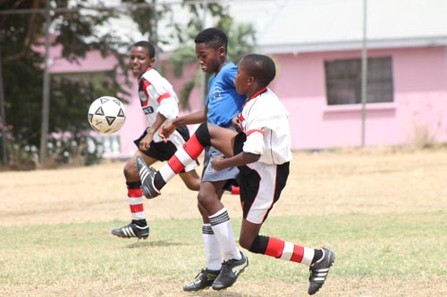 Sharon's striker Anthony Miller looks to control the ball as St Alban's Azari Williams challenges and goal-scorer Jaden Harrison (left) follows the play.