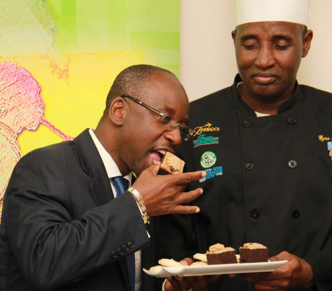 Minister of Sports Stephen Lashley tasting one of Ezra Beckles' desserts.