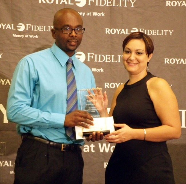 Roger Scott (left) receives his prize from Royal Fidelity Merchant Bank's Assistant Vice-President Jillian Nunes.