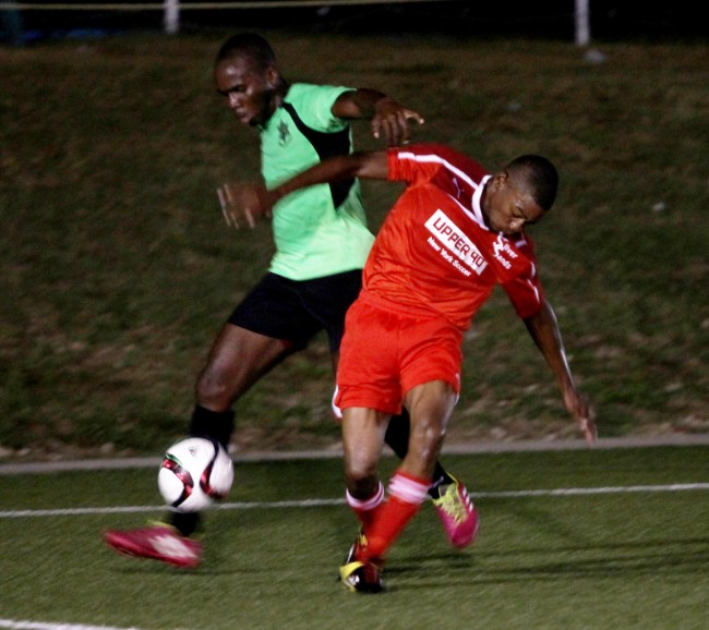 BDF's Joshua Rouse (in green) and Silver Sands' Bryan Newton challenge each other for the ball.