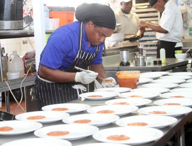 Chef Willis Griffith is a picture of concentration as he decorates these plates.