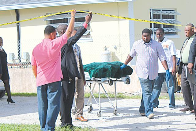 Mortuary services personnel remove the body of Roberton Williams, who was shot to death in Pinewood Gardens.