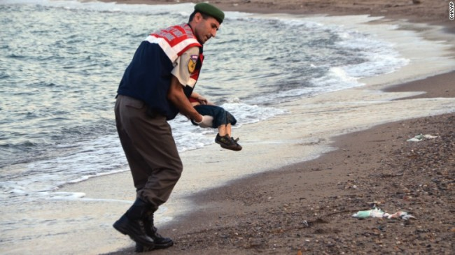 An officer in Bodrum, Turkey, carrying the body of three-year-old Alyan Kurdi, who was one of 12 refugees who drowned yesterday, during a failed attempt to sail to the Greek island of Kos.