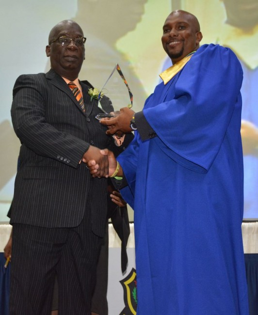 Erdiston 2015 graduating class valedictorian Dwight Carter receives his award from  Minister of Education Ronald Jones.