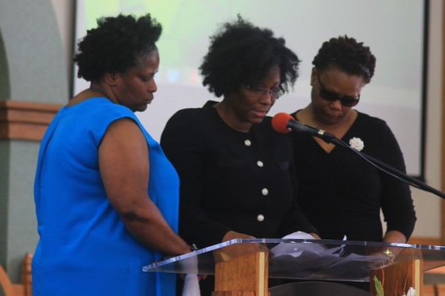Judy Lynton (left) and Sonja Lynton (right) lend support to their sister  Dr Wendy Hope who delivered the eulogy at their father's funeral service.
