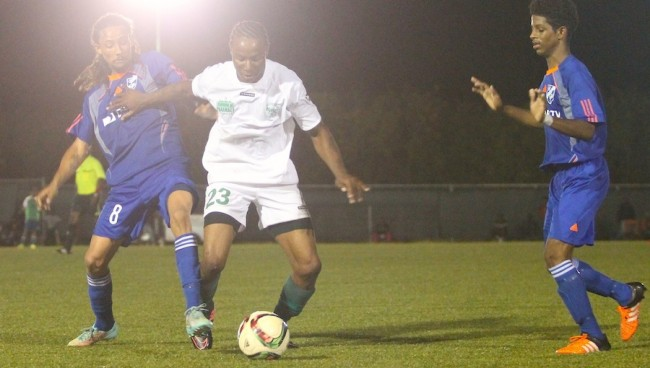 (From left) Trevor Mayers of Direct TV Paradise in an intense battle with national player and Weymouth Wales midfielder Rico Graham while Elijah Downey looks on. (Pictures by Morissa Lindsay).