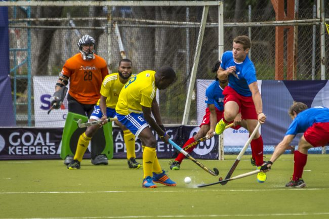 Che Warner (#8) is team tackled by US players as he tries to get off at shot.