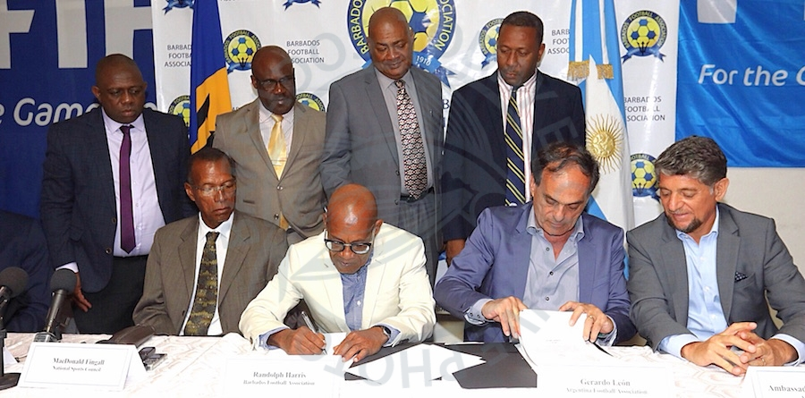 Barbados Football Association president Randolph Harris (second left) signs the MOU along with executive director of the Argentina Football Association Gerardo Leon (second right) while other officials look on.  (Picture by Morissa Lindsay)