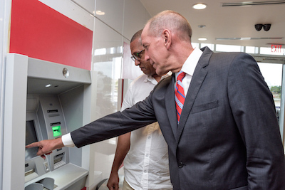 David Parks, Managing Director, Caribbean East, Scotiabank assisting Roger Thomas as he used one of the newly installed next generation ATMs - Intelligent Deposit Machines (IDMs) at the Warrens branch.