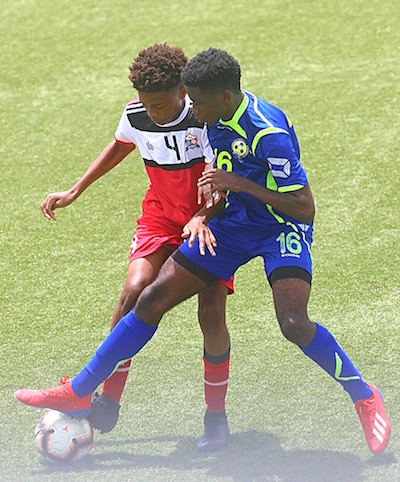 Barbados goal- scorer Aaron Cumberbatch (right) challenges Amadeus Aventurin of St. Maarten for ball possession.